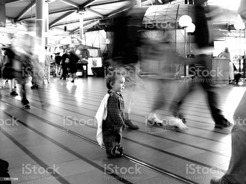 Toddler Standing in Middle of Building with People Walking By royalty-free stock photo