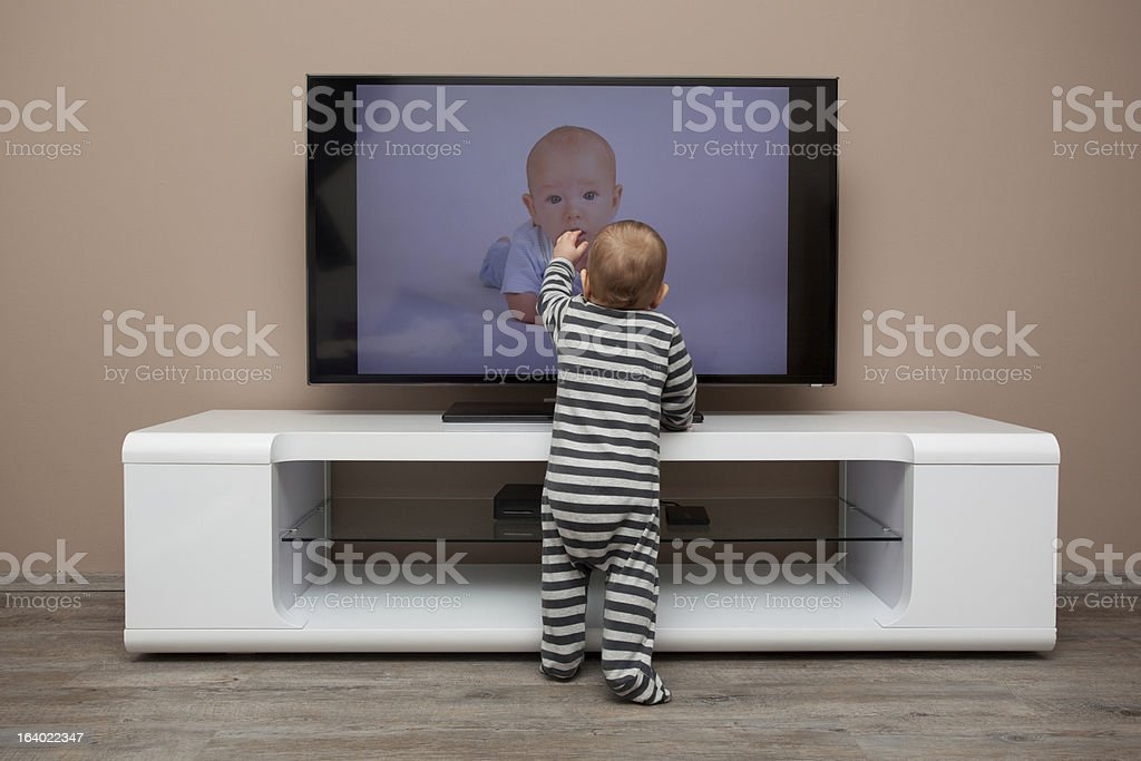 Toddler touching a baby on the television stock photo