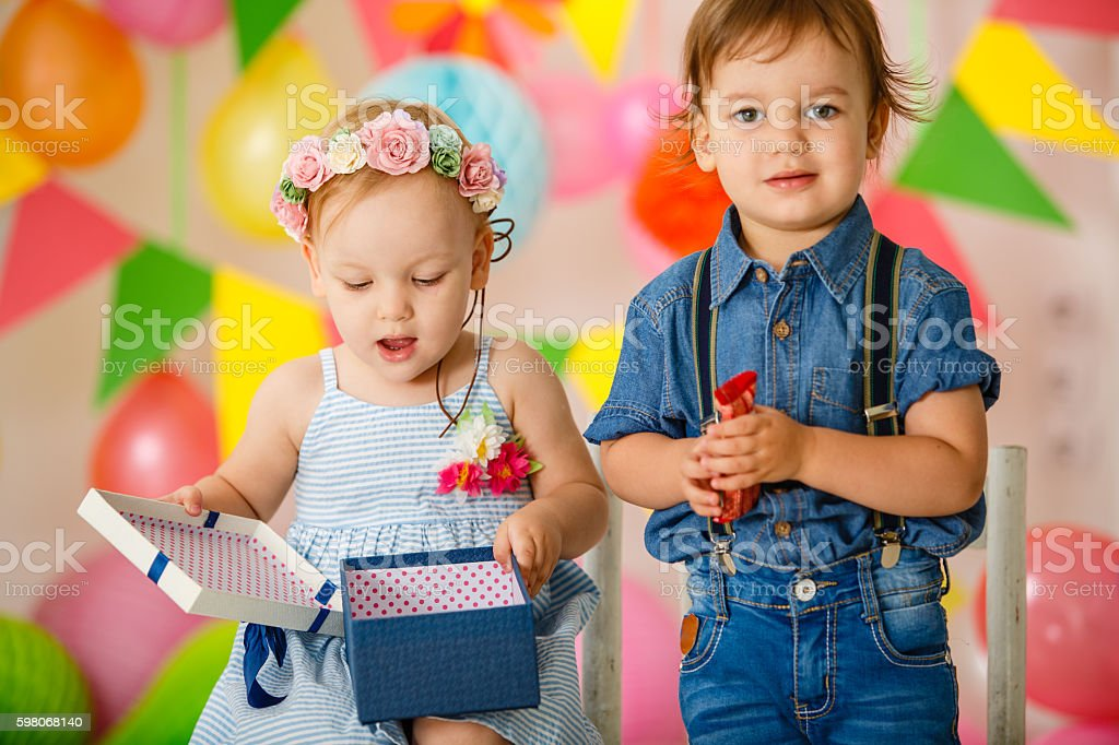 Toddler twins opening present at birthday party stock photo