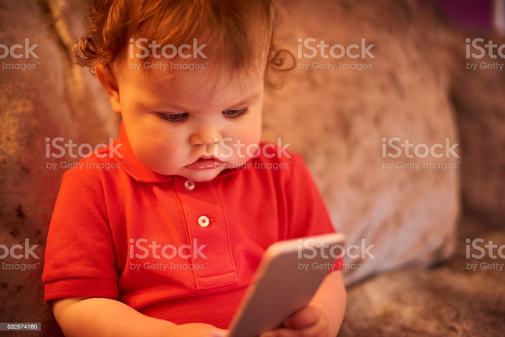 Toddler watching videos on mobile phone stock photo