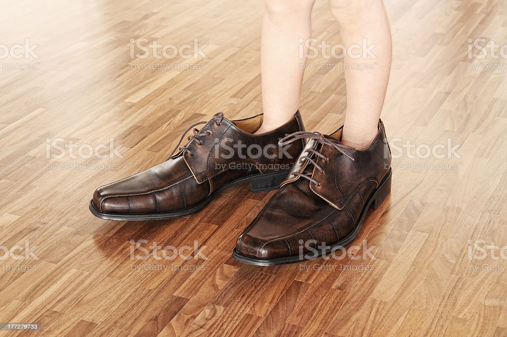 Toddler wearing adult shoes stock photo