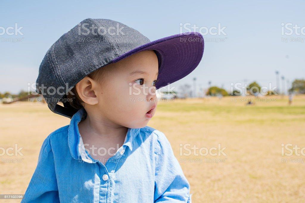 Toddler wearing an adult sized baseball cap stock photo