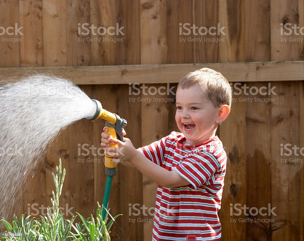 Toddler with garden hose spray royalty-free stock photo
