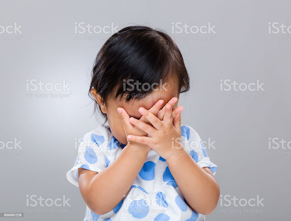 Toddler with hands over face stock photo