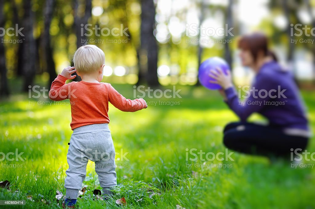 Toddler with his mother playing ball stock photo