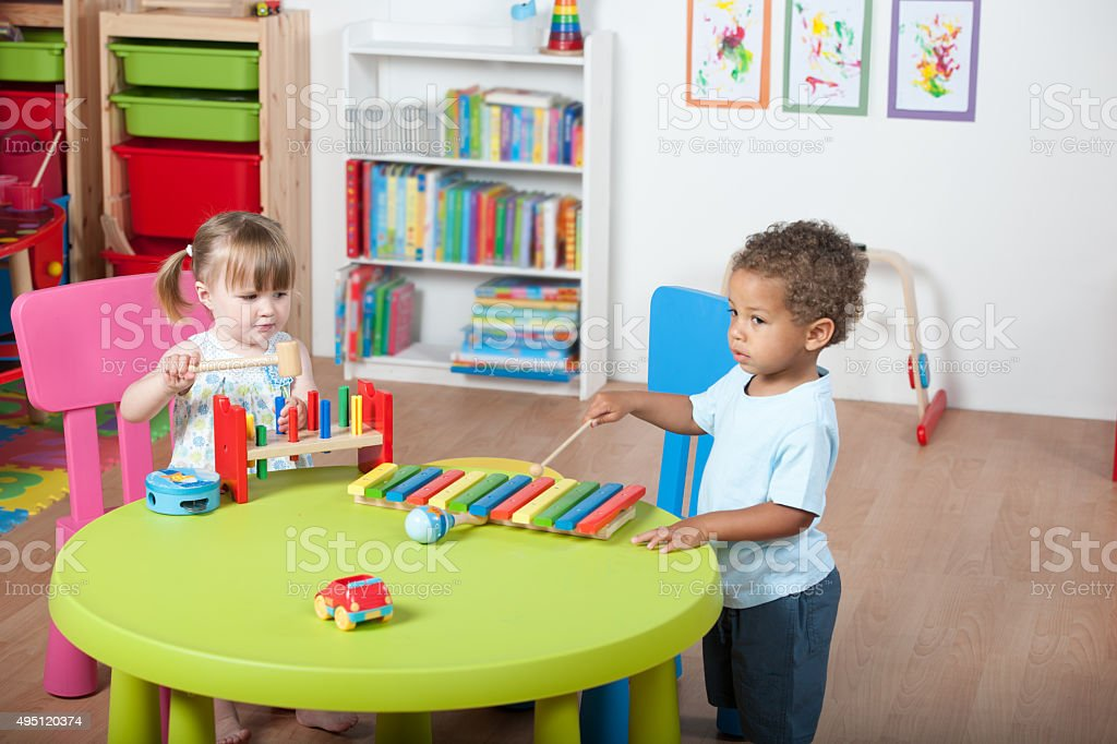 Toddlers Enjoying Music/ Playtime In A Nursery stock photo