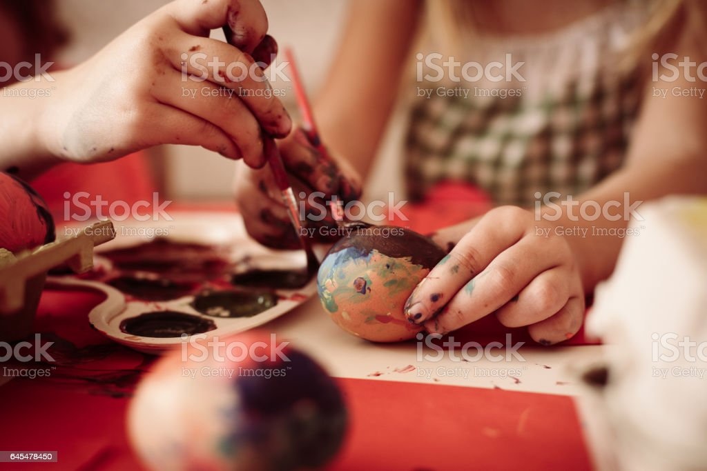 Toddlers having fun painting Easter eggs. stock photo