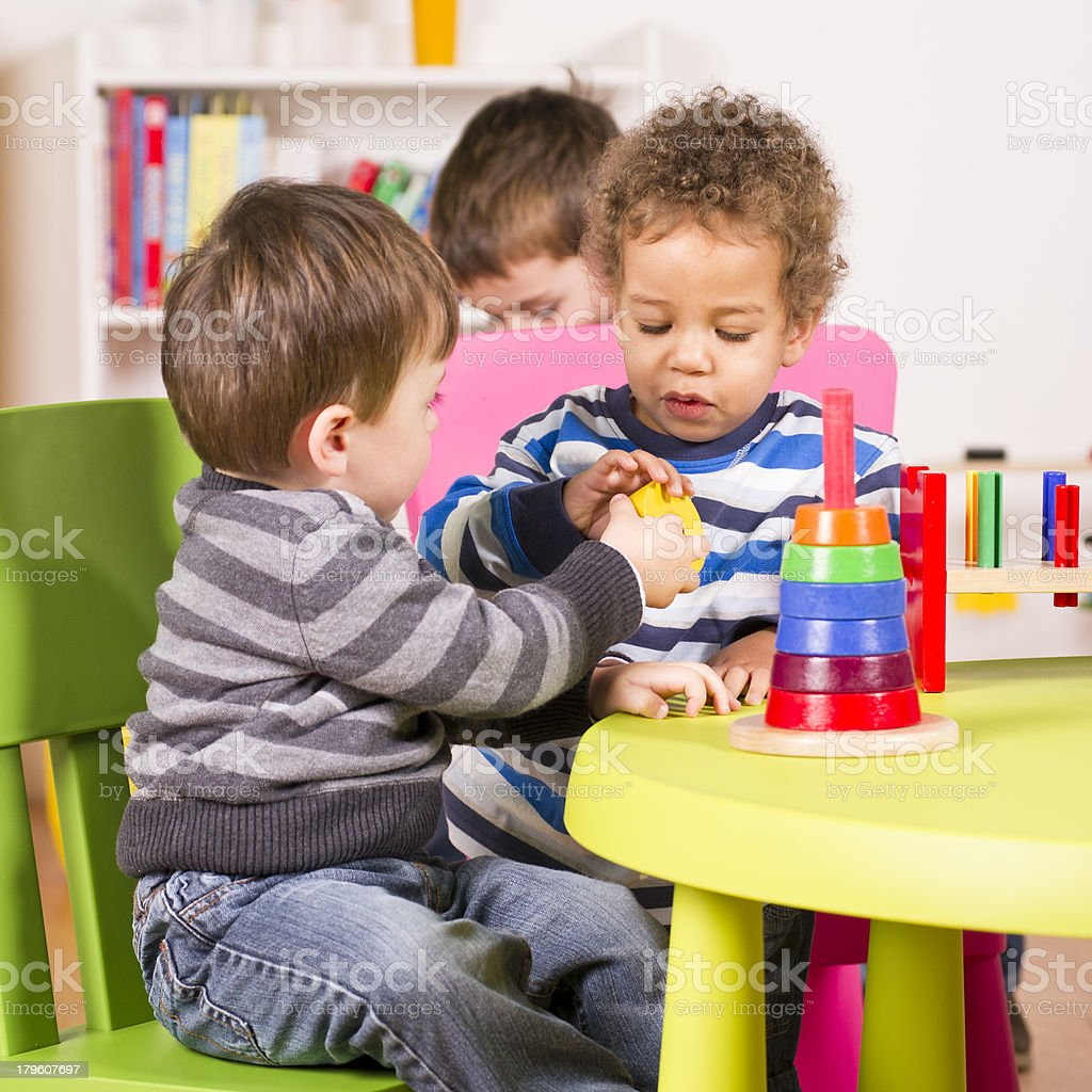 Toddlers helping and sharing in the playroom stock photo