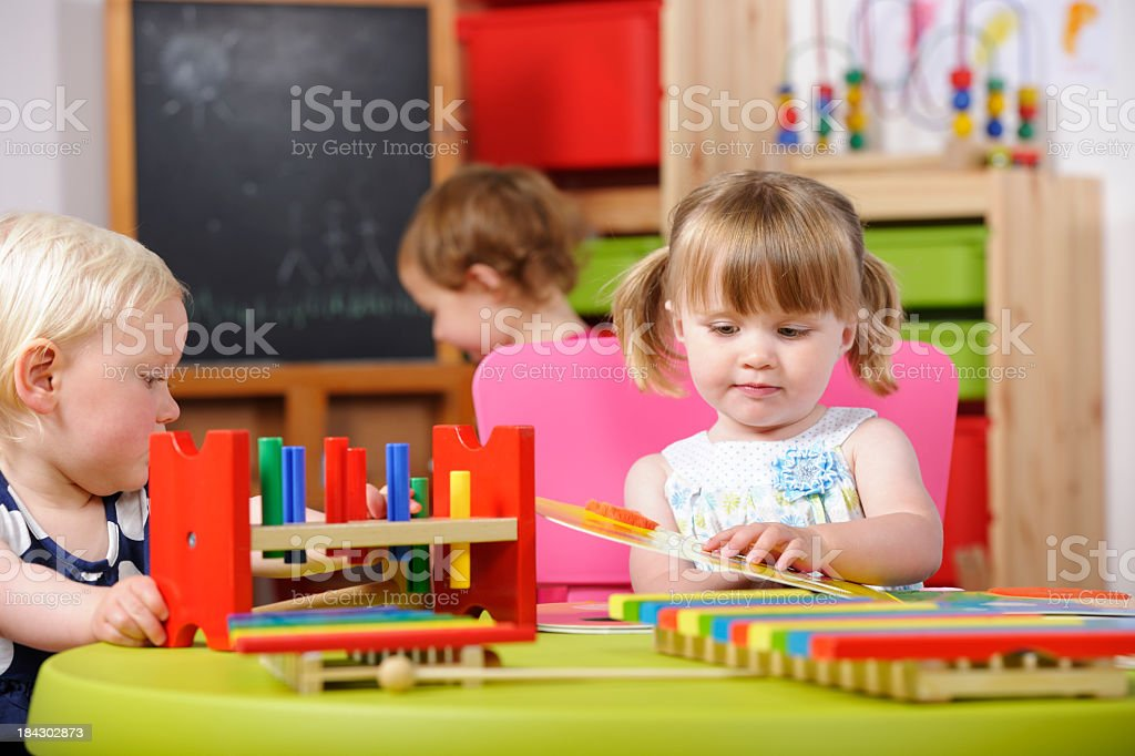 Toddlers Interacting During Playtime In A Nursery Setting royalty-free stock photo