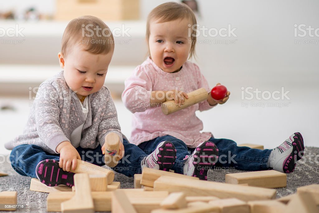 Toddlers Playing with Wooden Blocks stock photo