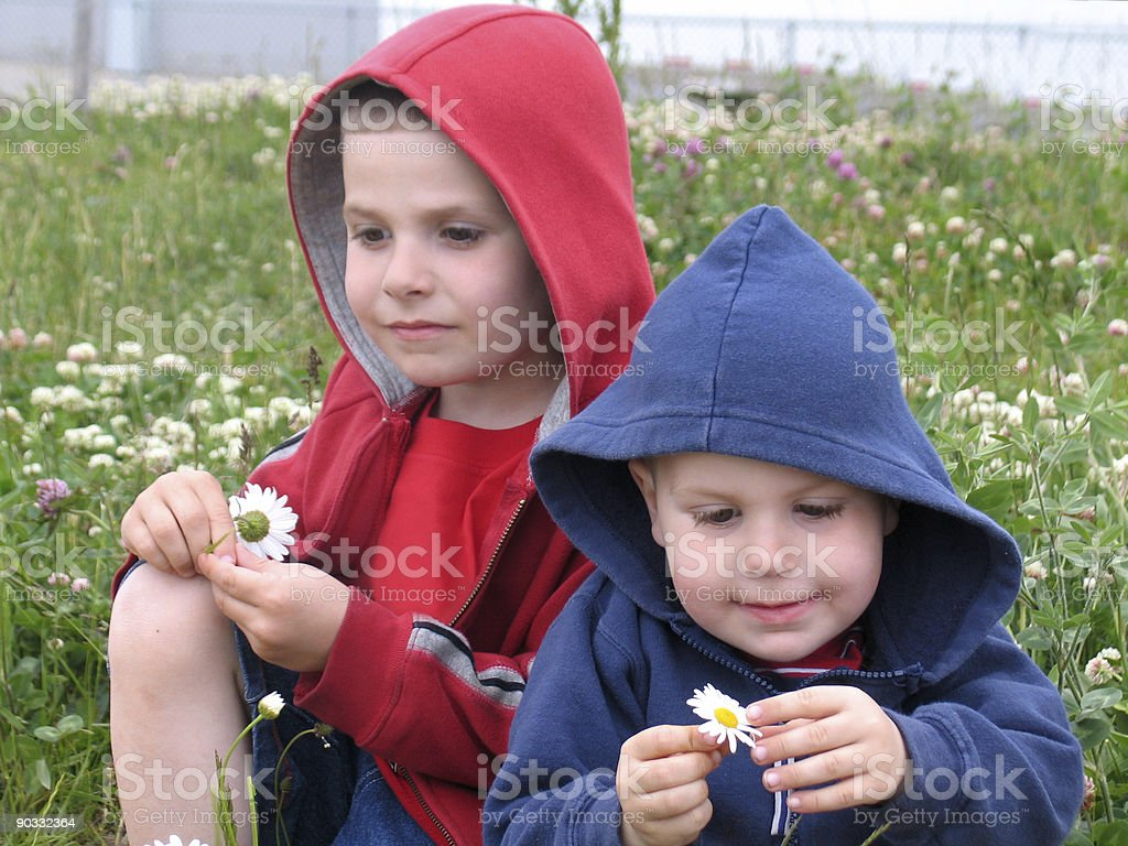 Toddlers Sitting at a Field | Children Deep in Thought stock photo