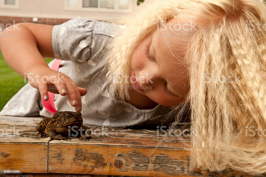 Toe head girl with crimped hair petting toad outside stock photo