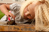 Toe head girl with crimped hair petting toad outside