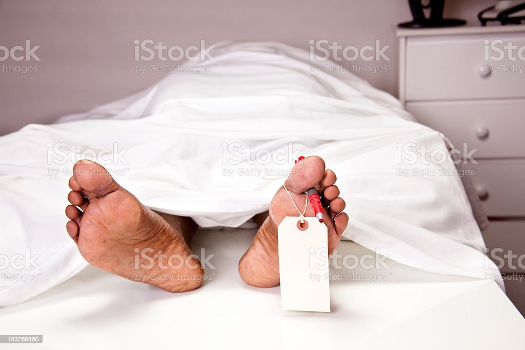 Toe tag and pen on human foot in morgue stock photo