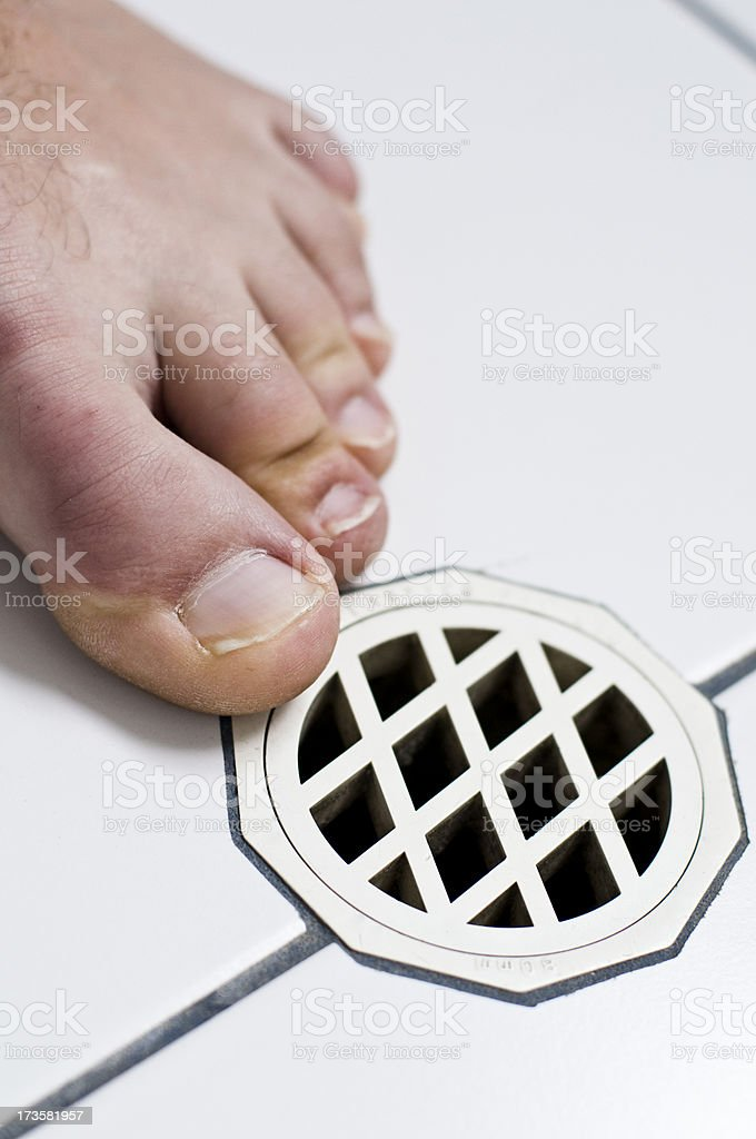 Toes foot bathroom drain white tiles. stock photo
