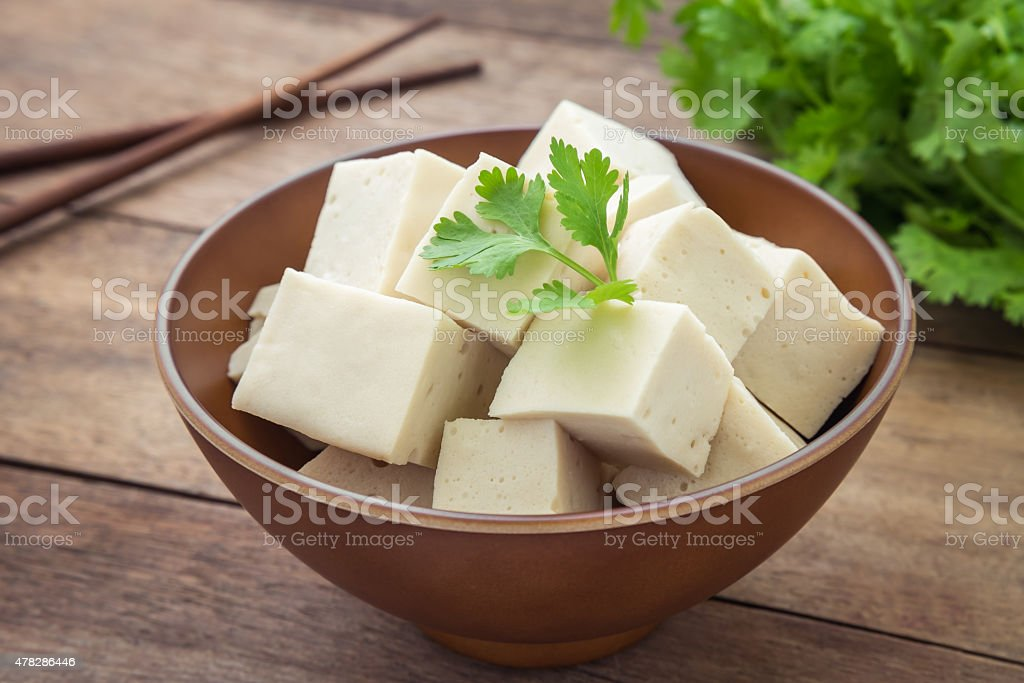 Tofu cubes in bowl and parsley stock photo