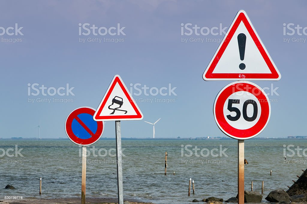 together of road signs next to sea stock photo