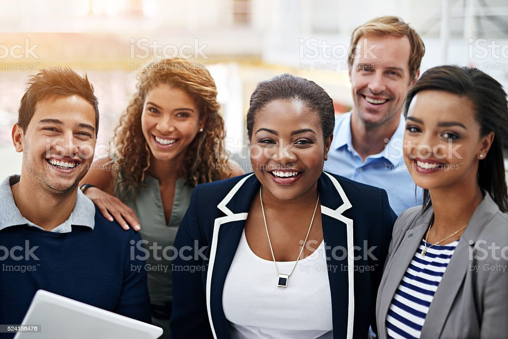 Portrait of a group of smiling coworkers standing in an office