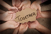 Together Written on Cardboard Being Held by Group of People