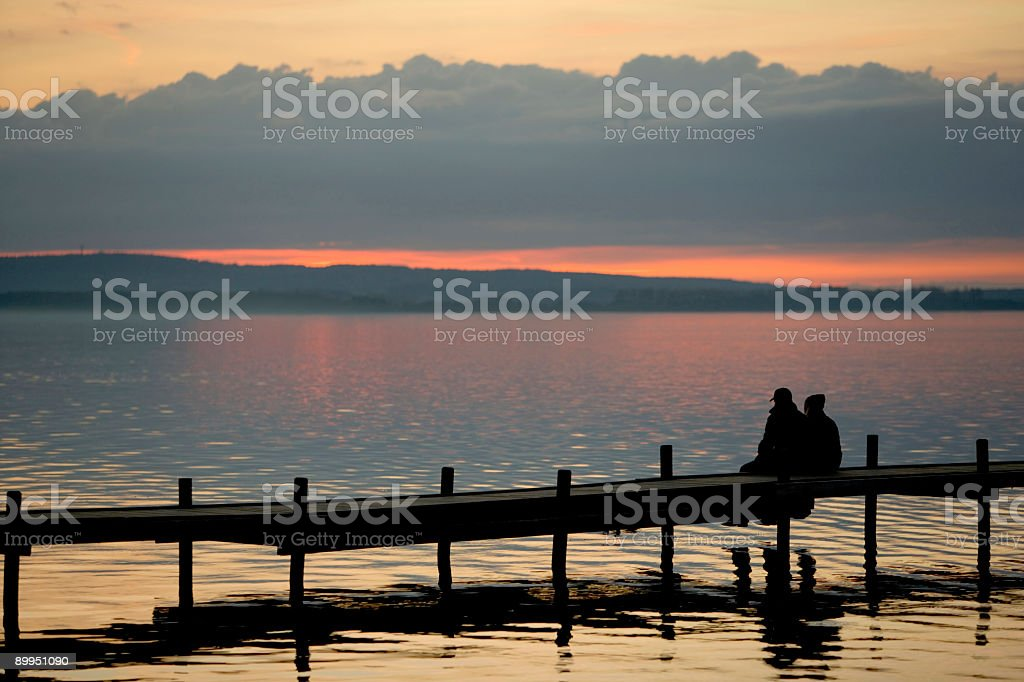 Togetherness - Couple sitting on lakeside jetty at sunset (XXL) royalty-free stock photo