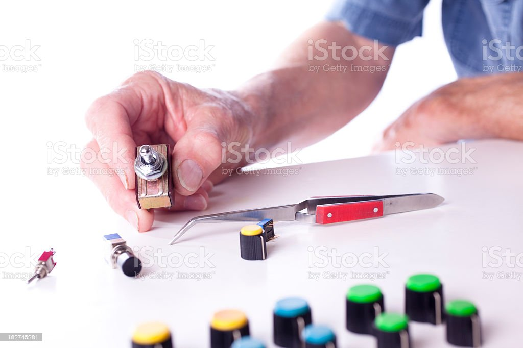 Toggle switch held by technician. on off stock photo
