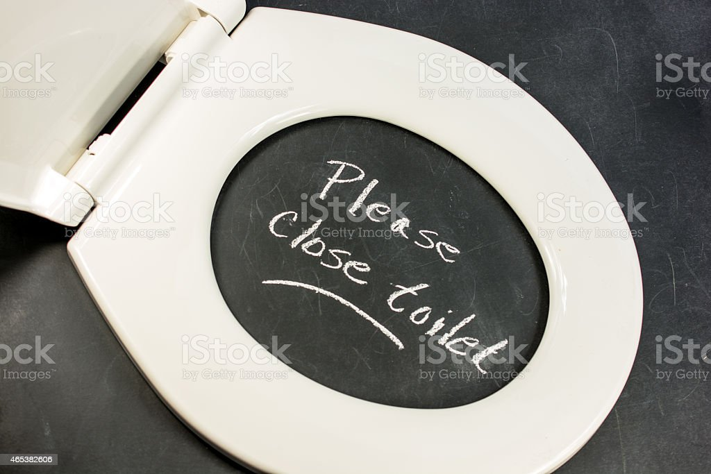 Toilet on blackboard- with words- please  put down lid. stock photo