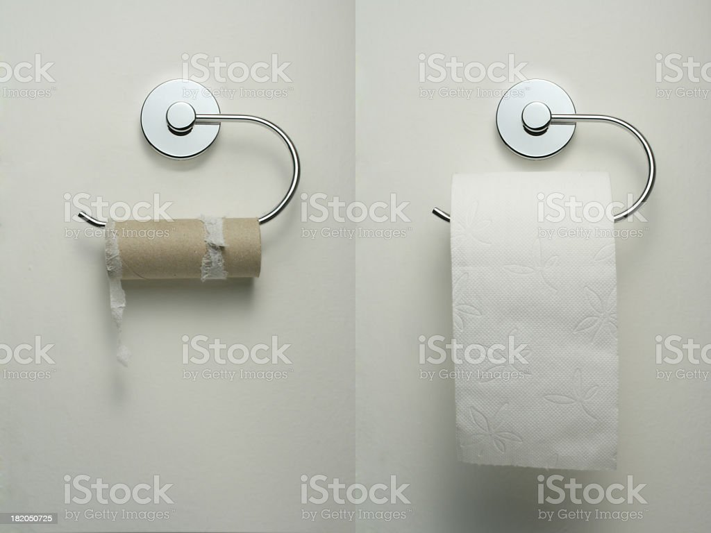Toilet paper holder with empty and new roll hanging up stock photo