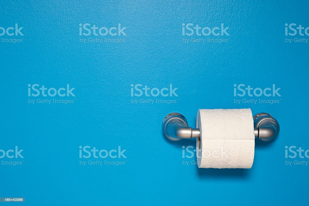 Toilet Paper On Blue Wall stock photo