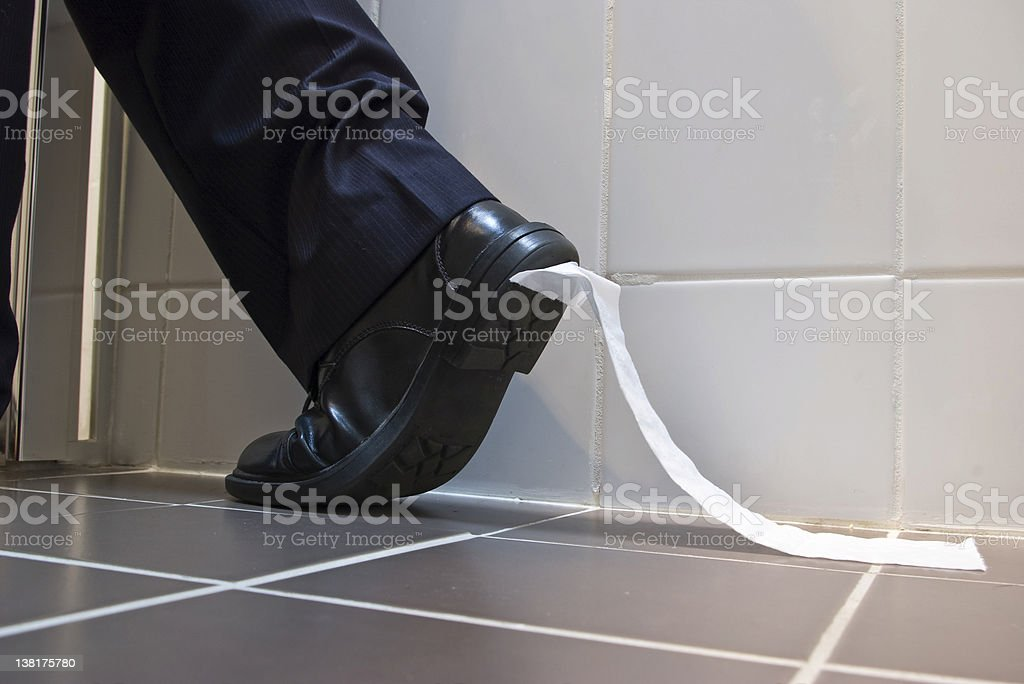 Toilet Paper stuck to sole of dress shoe stock photo