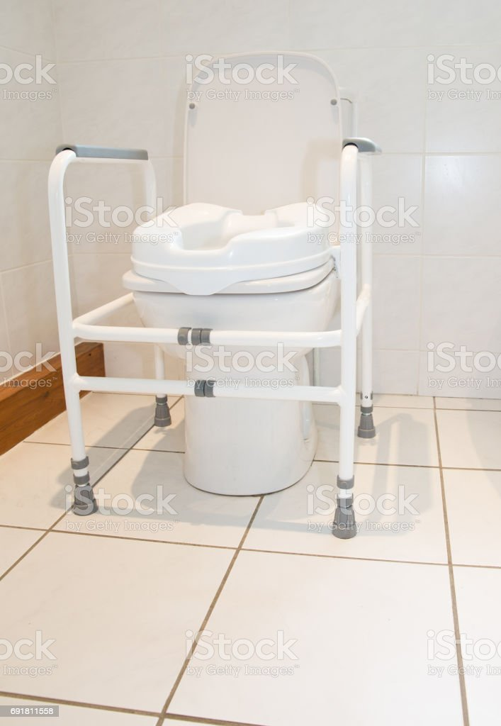 Toilet with raised seat to assist infirm or recovering patients stock photo