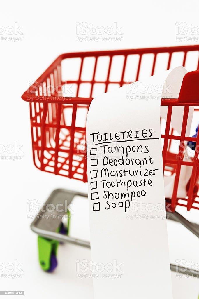 A miniature shopping cart contains a shopping list headed Toiletries...