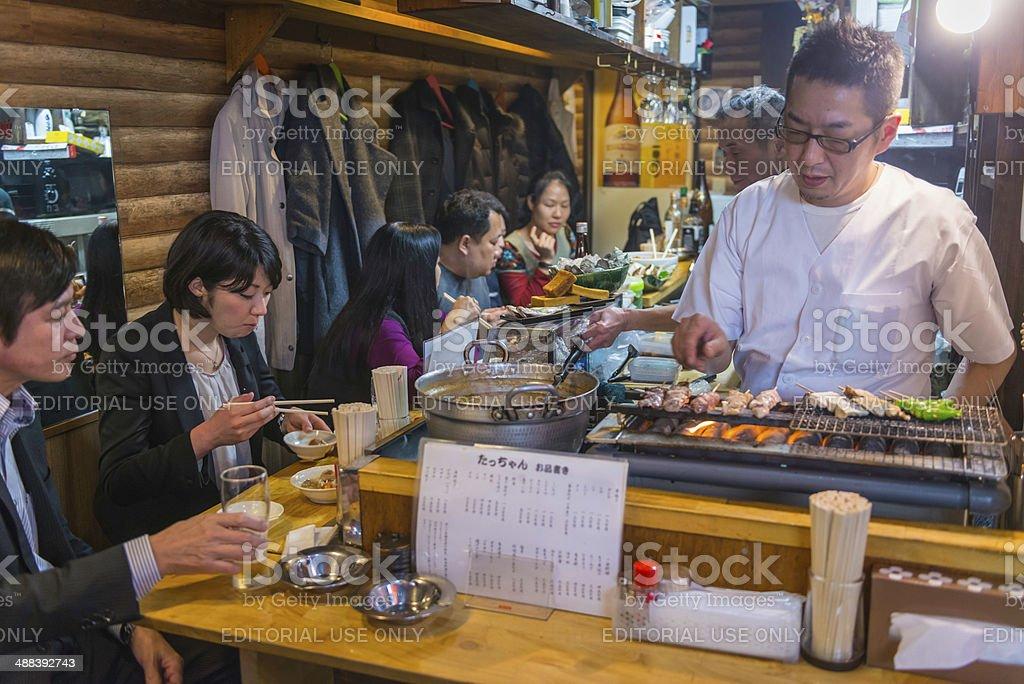 Tokyo cook customers in tradional alleyway bar restaurant Shibuya Japan stock photo