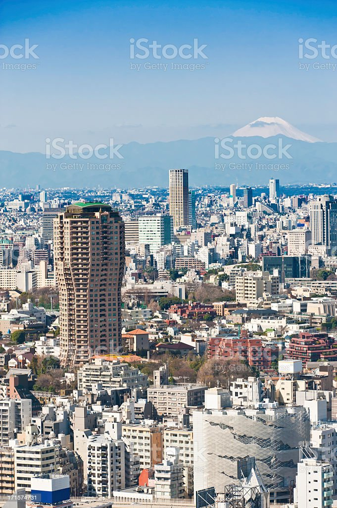 Tokyo Mt Fuji snowy cone overlooking crowded city skyscrapers Japan royalty-free stock photo