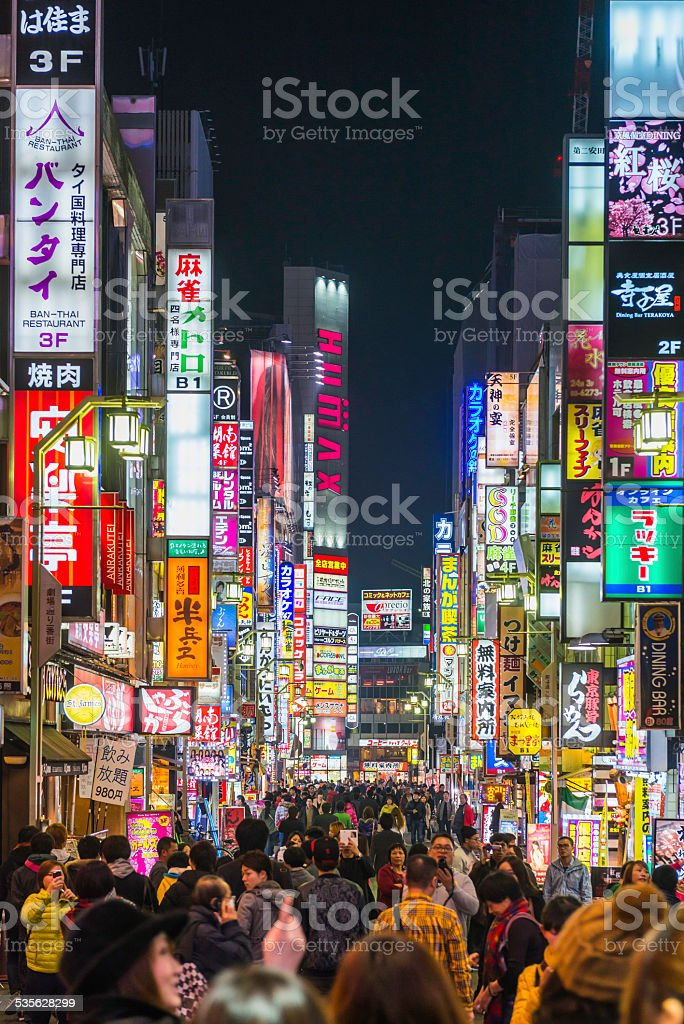 Tokyo nightlife crowded streets and colourful neon shopping signs Japan stock photo