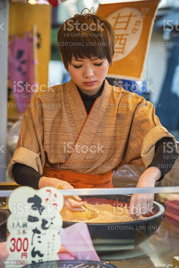 Tokyo woman preparing food Nakamise-dori market Senso-ji temple Asakusa Japan royalty-free stock photo