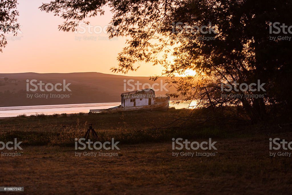 Tomales Bay sunrise and old deteriorating wooden boat stock photo