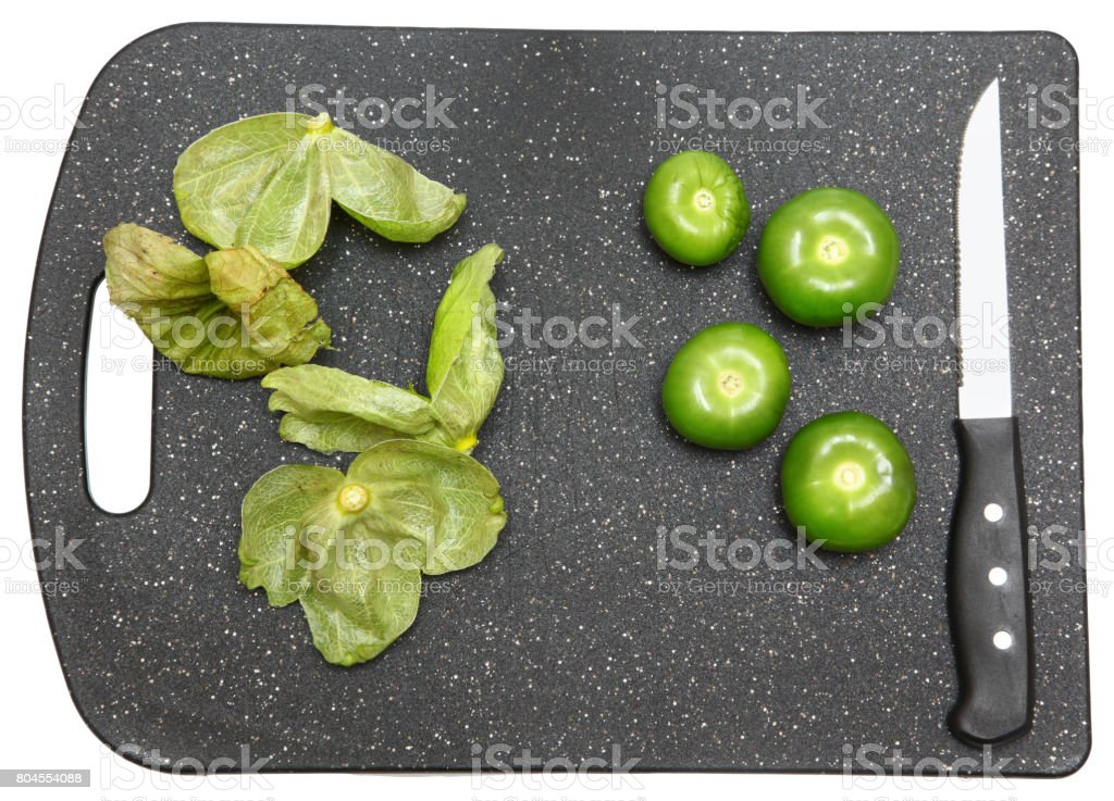 Tomatillo Whole on Cutting Board with Husk and Knife stock photo