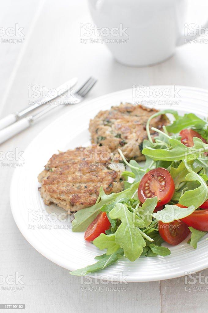Tomato and arugula salad with fish patties stock photo