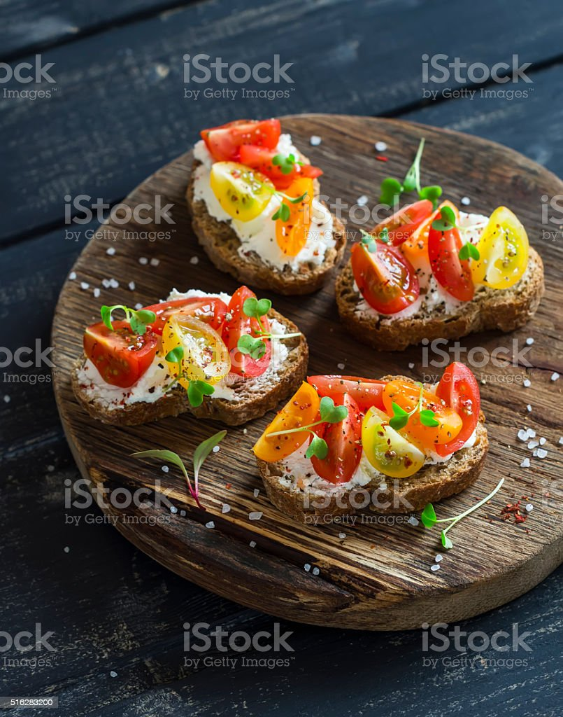 Tomato and cheese bruschetta on a rustic wooden cutting board stock photo