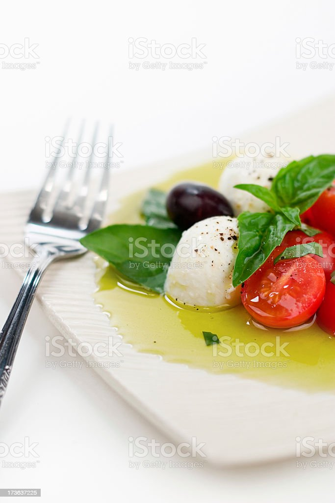 Tomato and mozzarella salad on a white plate with olive oil stock photo