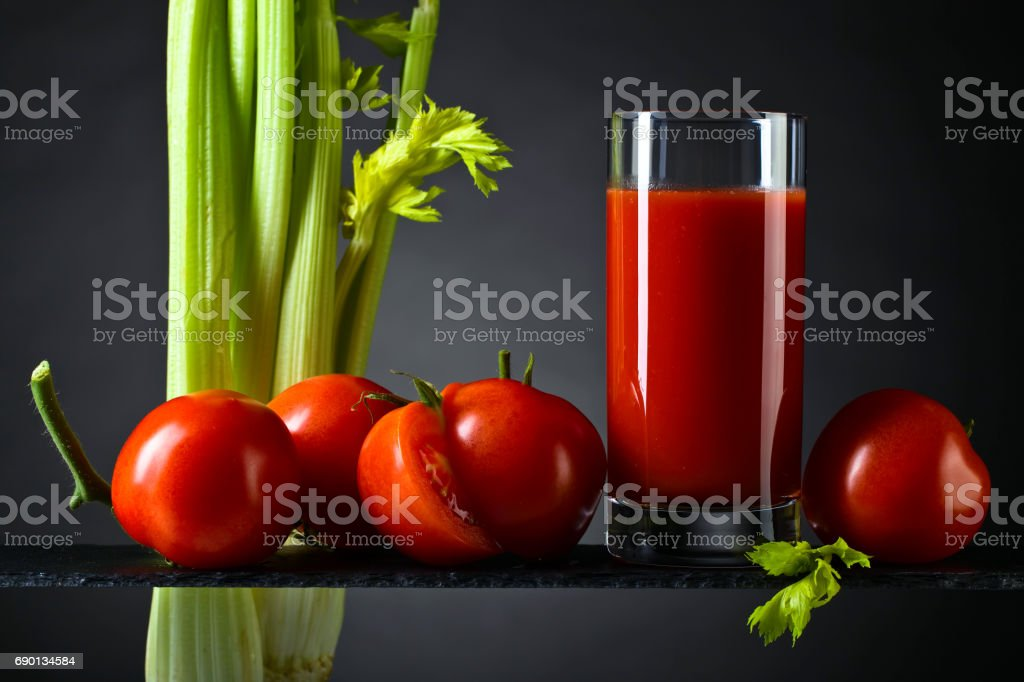 Tomato juice with tomatoes and celery sticks stock photo