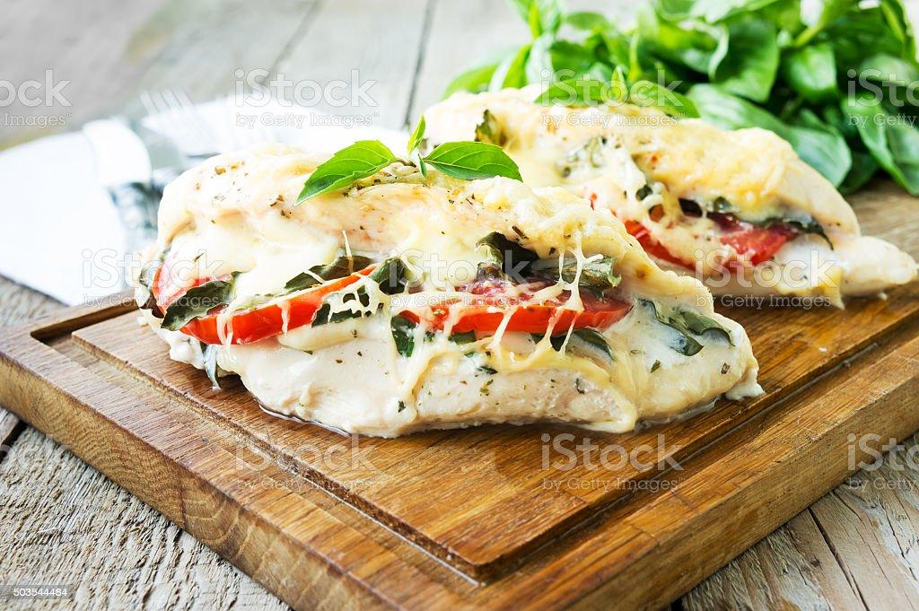 Tomato, mozzarella and basil stuffed chicken breasts stock photo