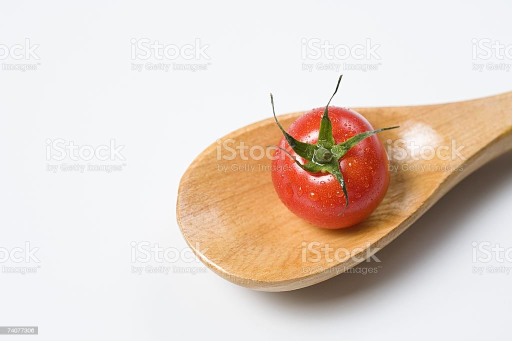 Tomato on a wooden spoon royalty-free stock photo