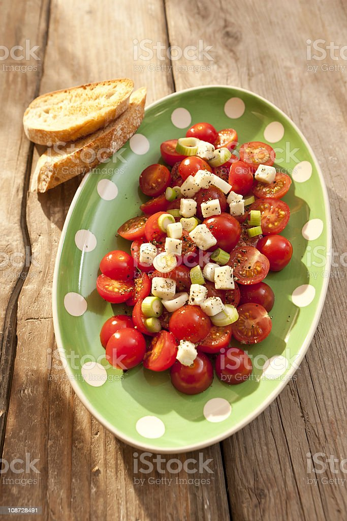 Tomato salad with spring onions and mozzarella royalty-free stock photo