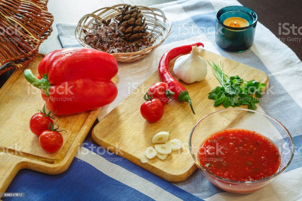 Tomato sauce adjika and vegetables on a wooden table stock photo