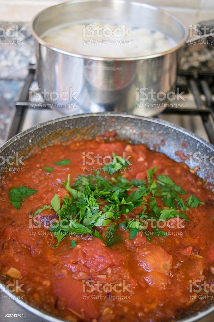 tomato sauce all'arrabbiata in panand potato dumplings in cookin stock photo