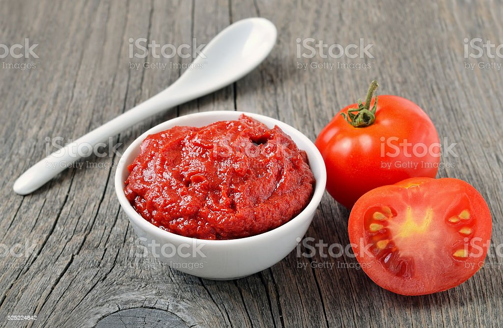 Tomato sauce in a white bowl and fresh tomatoes stock photo