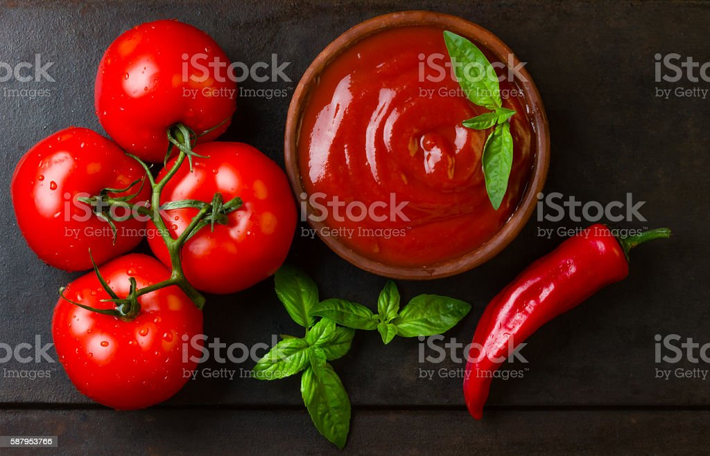 Tomato sauce salsa and ingredients dark stone background. Top view stock photo