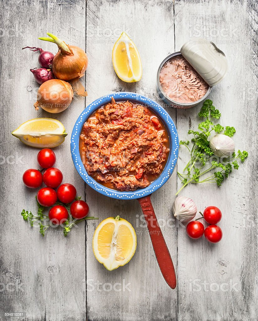 Tomato sauce with canned tuna in rustic pot and vegetables stock photo