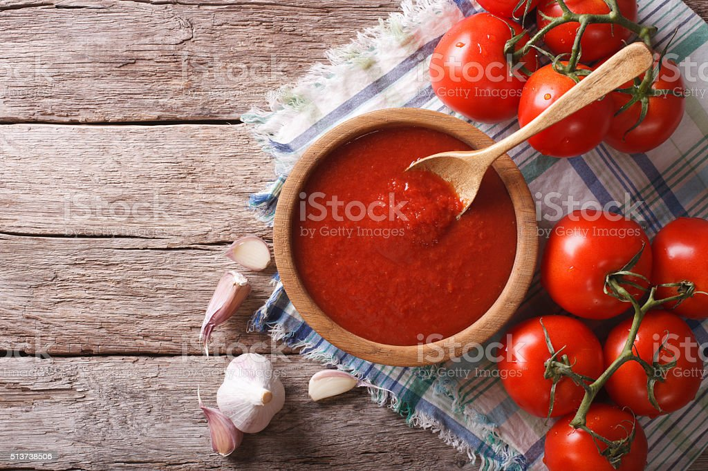 tomato sauce with garlic and basil in wooden bowl. horizontal stock photo